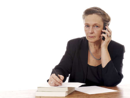 Mature woman sitting by table talking in cell phone and writing notes isolated on white background