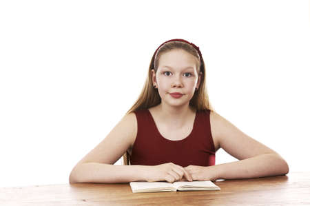 Beautiful young girl sitting by table and reading - isolated on white background