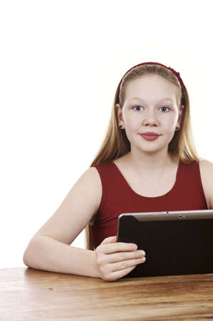 Beautiful young girl sitting by table with tablet computer - white background Stock Photo - 16336036