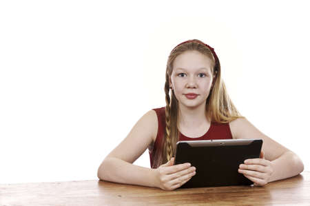 Beautiful young girl sitting by table with tablet computer - white background Stock Photo - 16336025