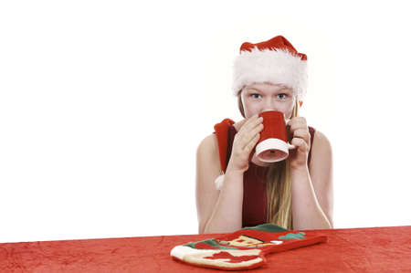 Beautiful young girl in christmas outfit drinking from mug - isolated on white background Stock Photo - 16336022