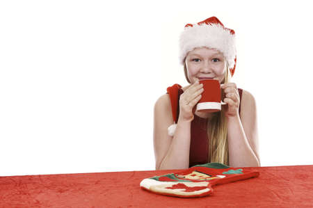 Beautiful young girl in christmas outfit drinking from mug - isolated on white background Stock Photo - 16325131