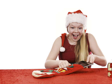 Beautiful young girl in christmas outfit retrieving present from traditional christmas stocking - isolated on white background Stock Photo - 16336014