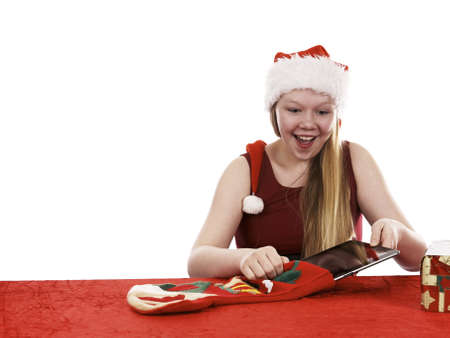 Beautiful young girl in christmas outfit retrieving present from traditional christmas stocking - isolated on white background Stock Photo - 16336008