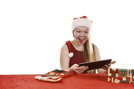 Beautiful young girl in christmas outfit retrieving present from traditional christmas stocking - isolated on white background Stock Photo - 16336023