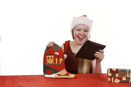 Beautiful young girl in christmas outfit retrieving present from traditional christmas stocking - isolated on white background