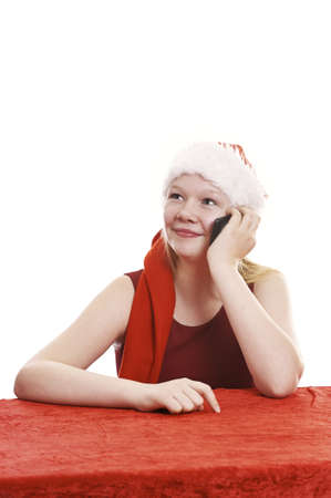 Beautiful young girl in christmas outfit talking in cell phone - isolated on white background photo
