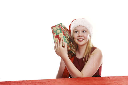 Beautiful young girl in christmas hat holding christmas present - isolated on white background photo