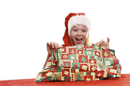 Beautiful young girl in christmas hat unpacking christmas present - isolated on white background photo
