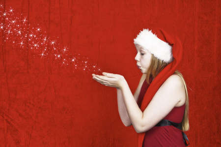 Beautiful young girl in christmas hat blowing stars from the palms og her hands on red background photo