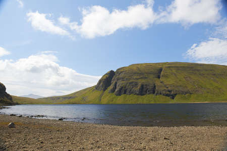 Scenic lake in the Faroe Islands on a summerday with blue sky and clouds Stock Photo