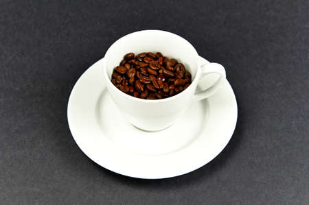 Coffee cup on a dish with coffe beans