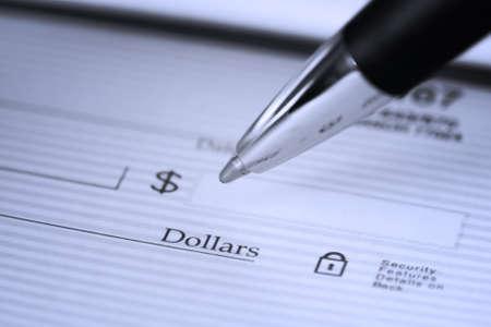 checkbook: Cerca de la pluma de rellenar un cheque en blanco