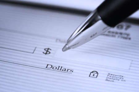Close up of pen filling in a blank check