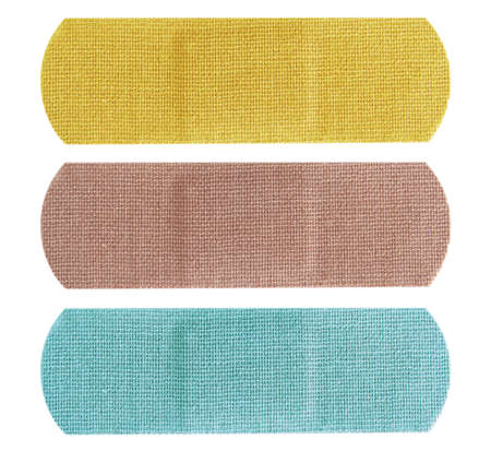 bandaid: Set of three colored bandages in blue, yellow and beige over white.