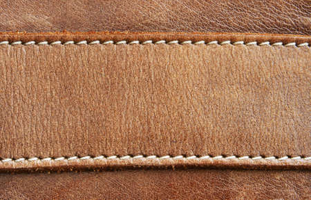 Close up of brown leather detail with white stitching.