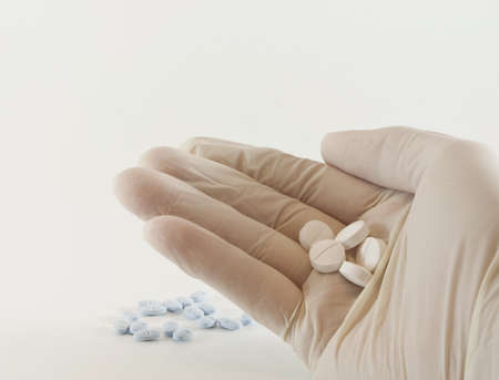 White latex gloved hand holding, counting and preparing medicinal prescription blue and white pills isolated on white background  Stockfoto
