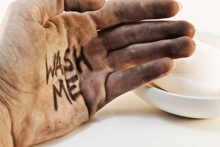 Close up of dirty caucasian bare hand with wash me written on palm and soap in background isolated on white background.