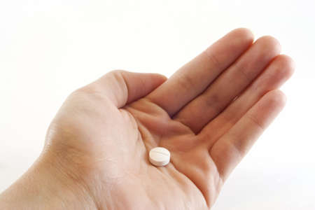 Bare female hand holding one white medicinal tablet in the palm of the hand. Stock Photo - 13642450