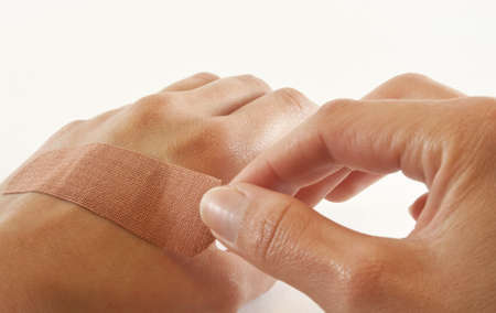 bandaid: One bare female hand sticking bandaid over cut on the other hand. Stock Photo