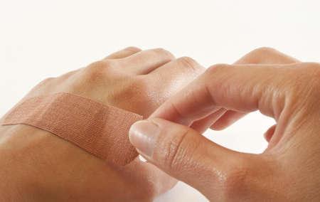 firstaid: Una adherencia desnudo mano femenina curita sobre corte en la otra mano. Foto de archivo