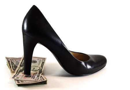 Womens sexy black high heeled shoe stepping on pile of fifty dollar US bills.