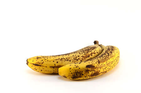 Two overripe rotting yellow bananas isolated on white background with plenty of copy space.