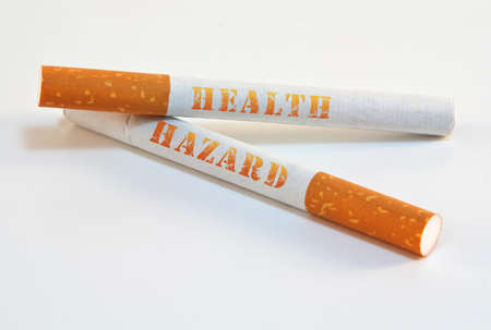 quit: Two cigarettes with health hazard written warning isolated on white background with plenty of copy space. Stock Photo
