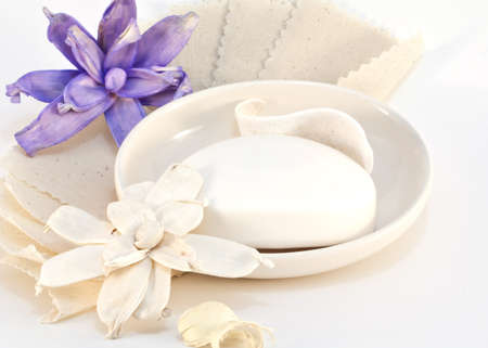 White bar soap in dish with beige and purple potpourri scented flowers on fabric backdrop isolated on white background.