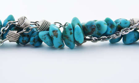 Close up of beautiful turquoise stones and shiny silver metallic chain necklace isolated on white background.