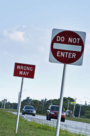 Wrong way and do not enter street signs in foreground with cars, road and traffic in background. Stock Photo