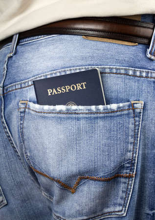 immigrate: Man standing with American blue passport in back pocket of denim blue jeans with copy space   Stock Photo