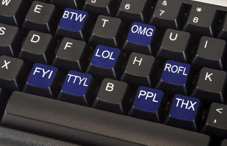 Black keyboard with text message slang words on keys including LOL, OMG, BTW, ROFL, FYI, TTYL, PPL and THX to illustrate fast paced social networking lifestyle concept  Stock Photo