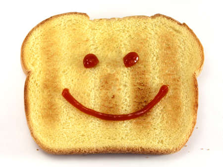 Single piece of toasted bread with a drawn happy face isolated on white background  photo