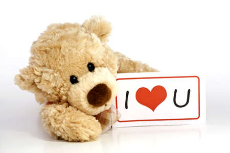 Cute furry brown teddy bear laying down holding an I Love You sign isolated on white background with copy space  photo