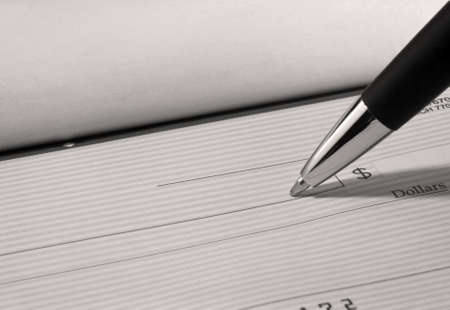 Close up of pen filling out a personal bank check with copy space  Stock Photo - 13873378