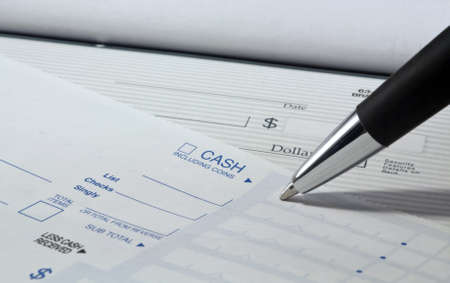 Close up of pen filling out a personal banking deposit slip with check in background and copy space