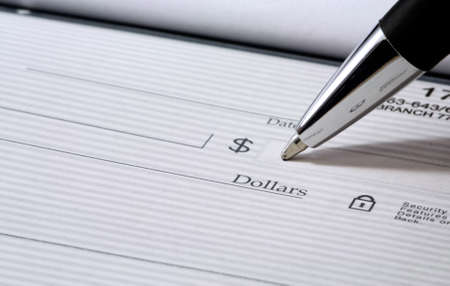 Close up of pen filling out a personal bank check with copy space