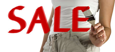 Young womans hand holding a brush painting a red sale sign on glass isolated on white background with copy space  photo