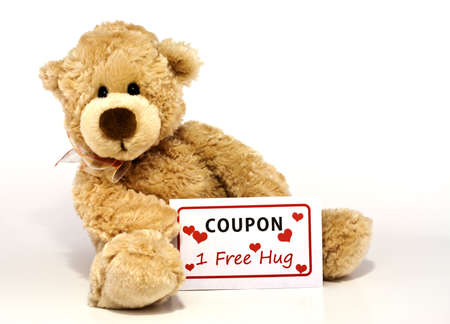 Cute furry brown teddy bear sitting and holding a coupon for one free hug isolated on white background with copy space
