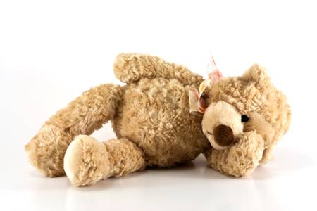Cute furry brown teddy bear laying down sick holding his head isolated on white background with copy space  photo