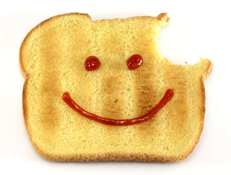 Single piece of toasted bread with a bite and drawn happy face isolated on white background