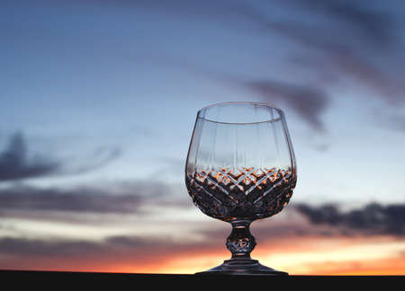 Crystal stem glass against beautiful sunset sky background with copy space  photo