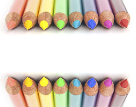 Set of rainbow multi colored pencils lined up on top and bottom as a border on blank white background with copy space