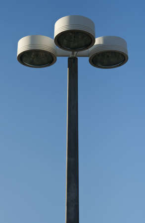 lamp post: Centered outdoor lamp post or light pole with three lamp heads against bright blue sky with copy space