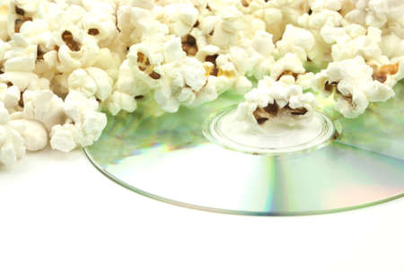 White fluffy tasty popcorn spilling over a shiny dvd movie disc isolated on white background with copy space  photo