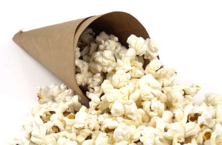 White fluffy tasty popcorn spilling from a brown paper cone isolated on white background with copy space