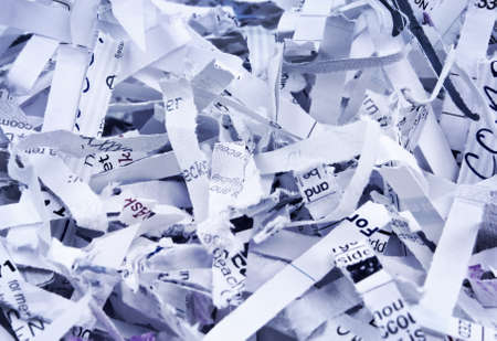 Close up of textured heap of shredded confidential papers with blue   photo