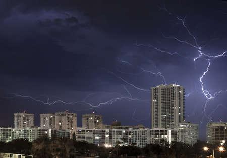 Scena di notte urbana della città con il grande fulmine che accende il cielo tempestoso nuvoloso Archivio Fotografico - 14192693