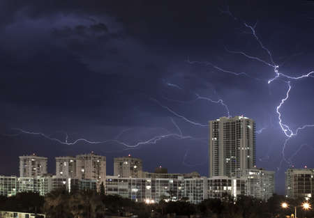 Urban city night scene with large lightning bolt lighting up the cloudy stormy sky  Stock Photo